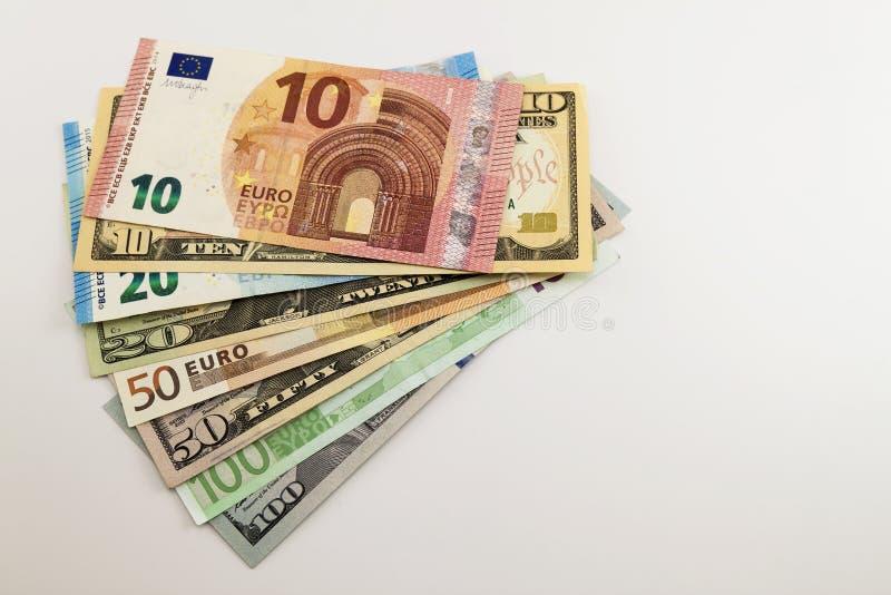 US dollarräkningar och euroräkningar fördelade blandat på vit bakgrund royaltyfria bilder