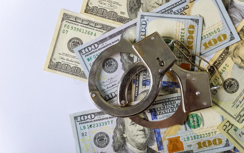 100 US dollars banknotes of counterfeit money and handcuffs. 100 US dollars banknotes of counterfeit money and police handcuffs, illegal, counterfeiting, forgery royalty free stock photo