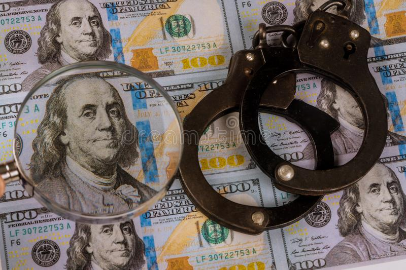 100 US dollars banknotes under magnifying glass of counterfeit money and handcuffs. 100 US dollars banknotes under magnifying glass of counterfeit money and royalty free stock photography