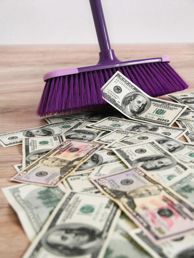 US dollars and broom. Broom cleaning US dollars banknotes royalty free stock photo