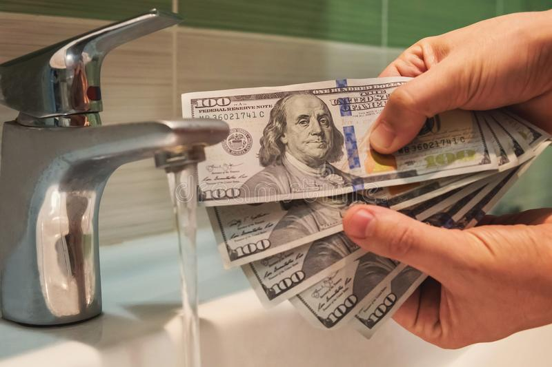 US dollars hung under running tap water stock photo