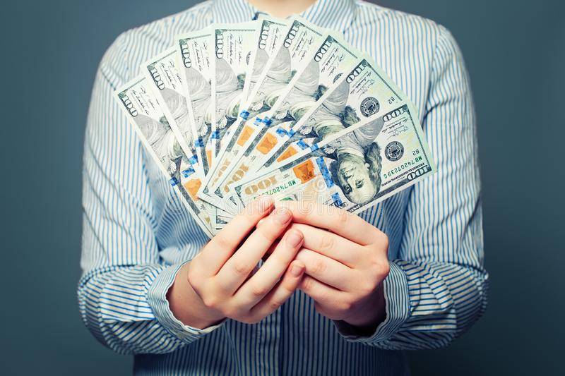 US dollars money concept. Hands with cash money on blue background royalty free stock image
