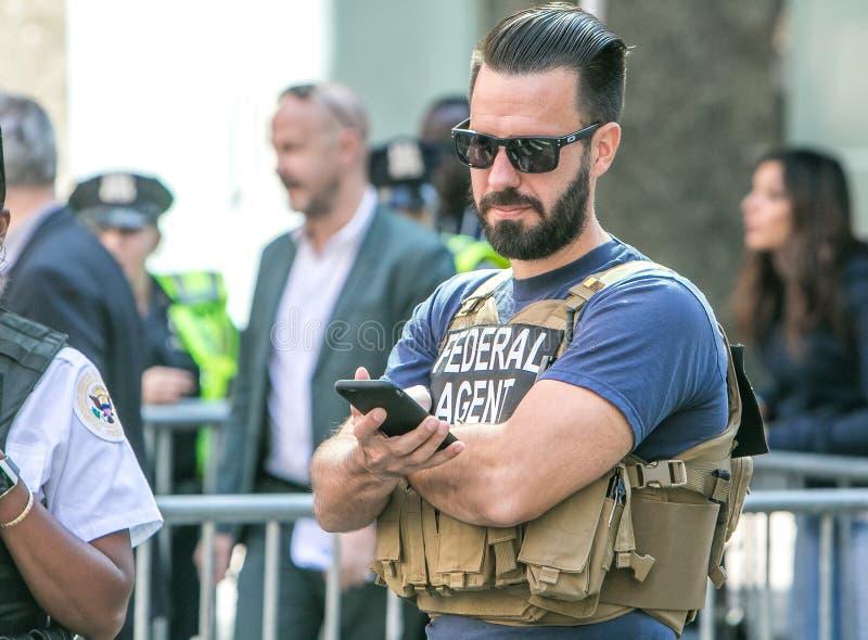 US federal agent checking his phone fotografia de stock royalty free
