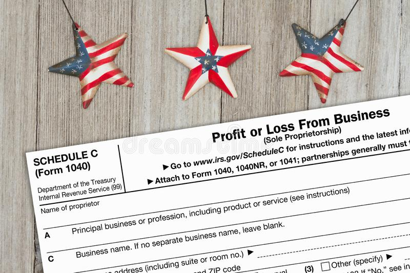 A US Federal tax 1040 schedule C income tax form. On weathered wood with USA stars royalty free stock photos