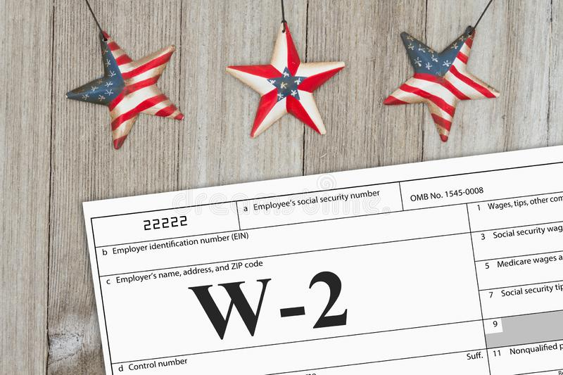 A US Federal tax W2 income tax form. On weathered wood with USA stars royalty free stock images
