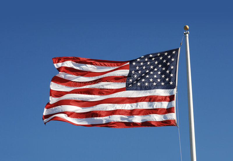 US flag. Waging US flag against blue sky royalty free stock photo