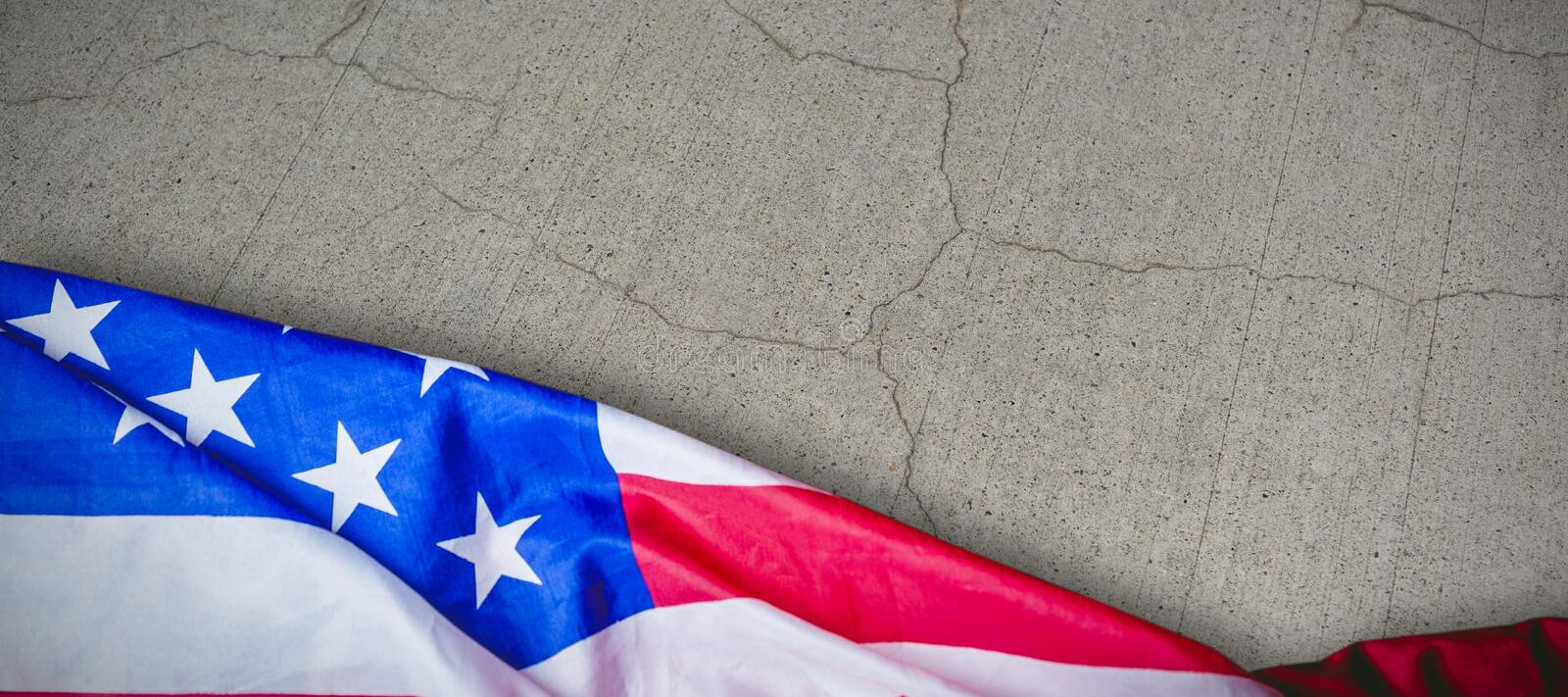 Composite image of us flag. US flag against gray cracked concrete wall stock images