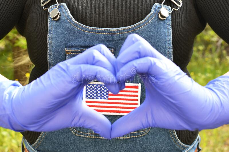 US flag batch. Focus on US flag batch on a jeans jumper with woman`s hands in gloves making love gesture stock images
