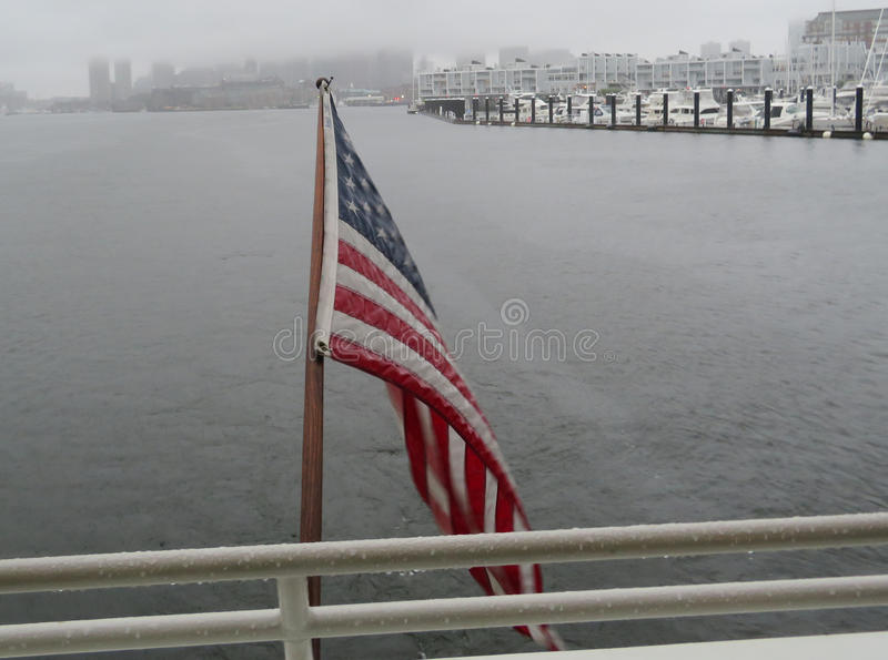 Us Flag on Boat with Foggy Shore. US Flag on a boat in Boston Harbor with fog on shore royalty free stock images