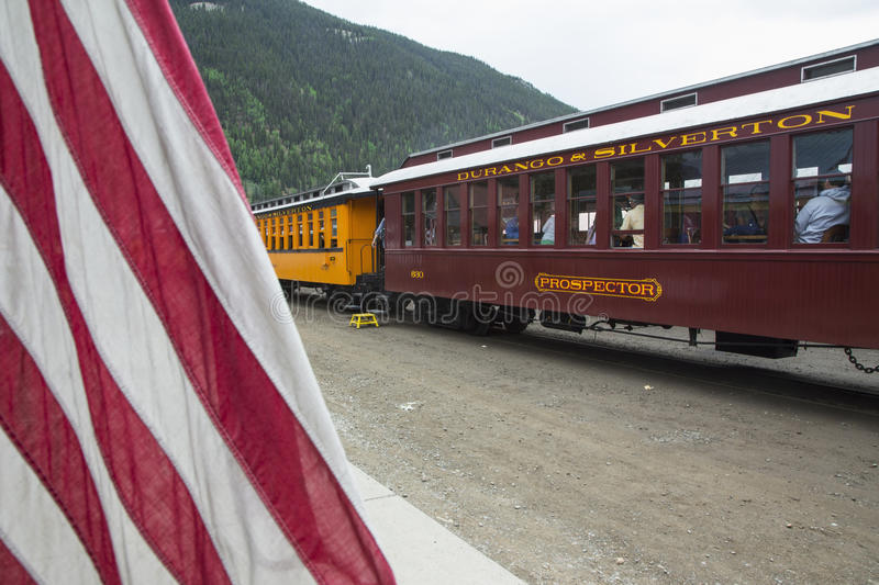 US Flag and Durango and Silverton Narrow Gauge Railroad Steam Engine Train, Silverton, Colorado, USA royalty free stock images