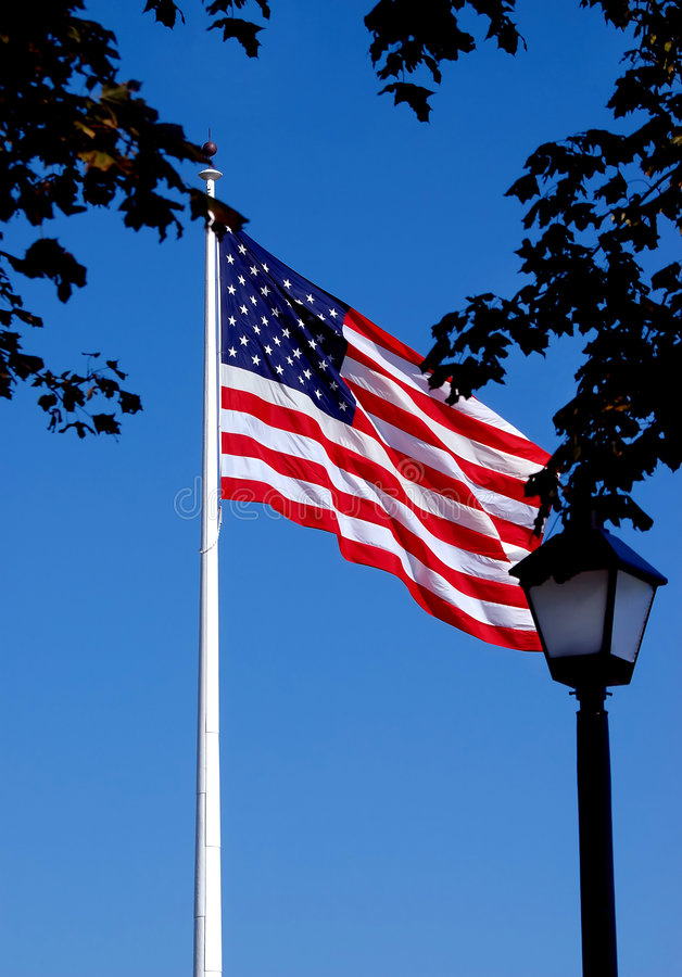 US Flag Flying. A United States of America flag flying high at the top of a flag pole royalty free stock photos