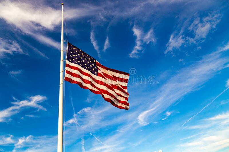 US Flag Flying at Half-Mast. USA Flag Flying at half-staff in blue sky stock photo