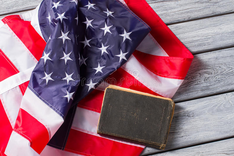 US flag beside old book. Book laying on national flag. Constitution of United States. Strict laws guarantee safety stock photo