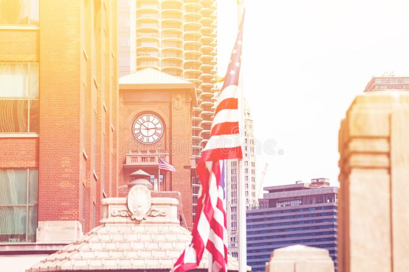 US flag over clocktower in downtown Chicago. US flag over clocktower in downtown City of Chicago, Illinois, USA royalty free stock photo