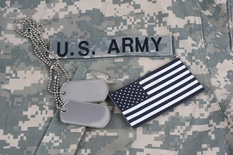 US flag patch with dog tag on Army Combat Uniform. Background stock photos
