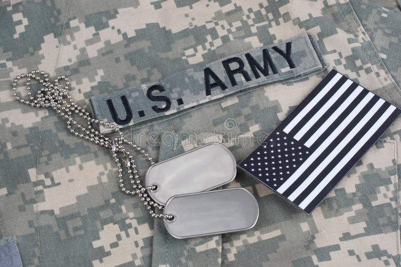 US flag patch with dog tag on Army Combat Uniform. Background stock photo
