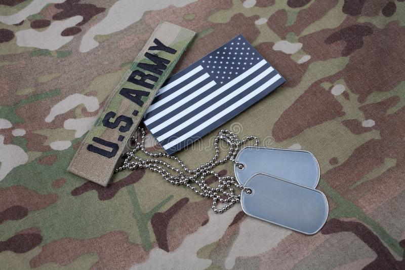 US flag patch with dog tag on US ARMY multicam uniform. US flag patch with dog tag on US ARMY multicam camouflage uniform royalty free stock photography