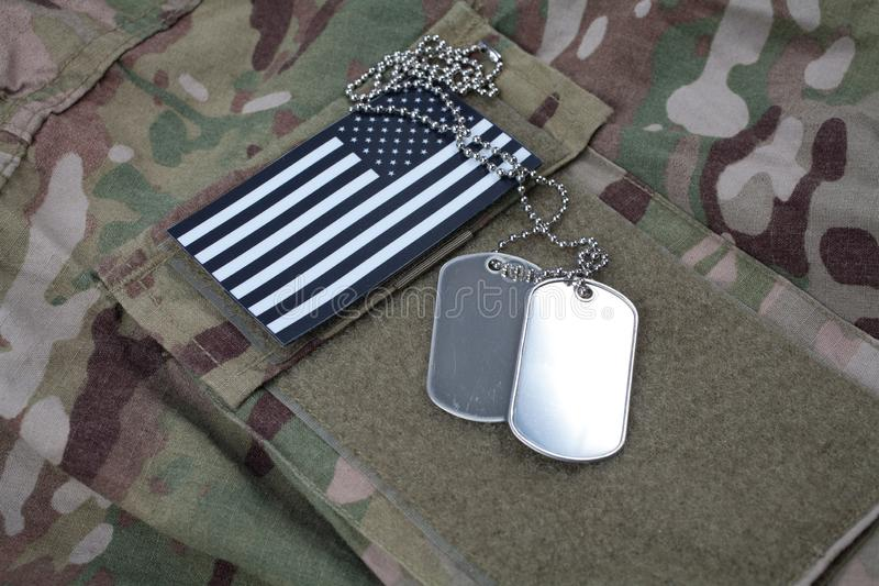 US flag patch with dog tag on US ARMY camouflage uniform. US flag patch with dog tag on US ARMY multicam camouflage uniform stock images