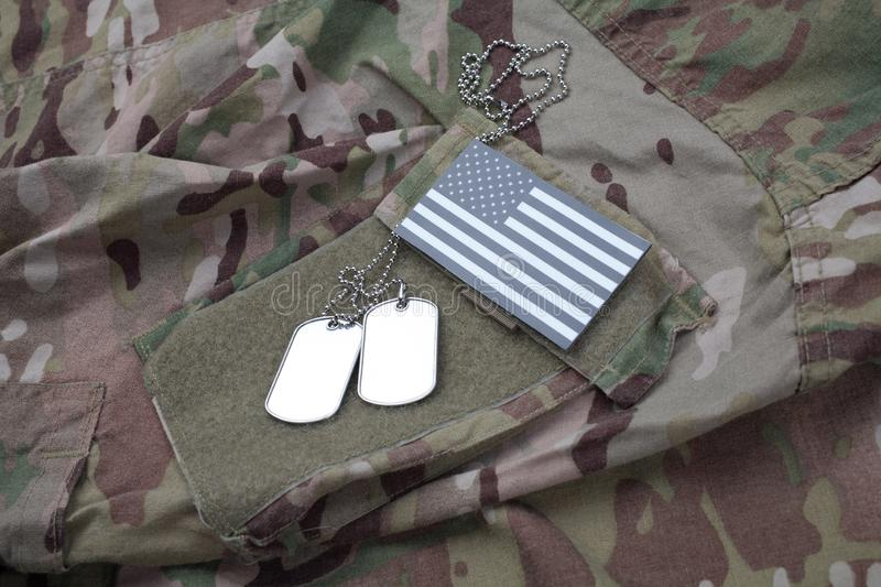 US flag patch with dog tag on US ARMY camouflage uniform. US flag patch with dog tag on US ARMY multicam camouflage uniform royalty free stock photo