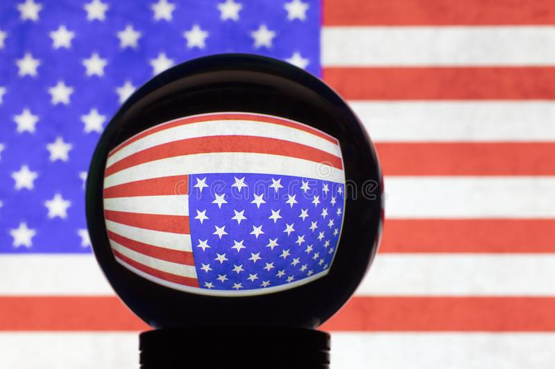 US flag in reflection on a crystal ball. Against a blurred American flag royalty free stock photo
