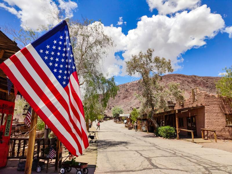 US flag waving, Calico ghost town background, blue sky, sunny spring day stock photography