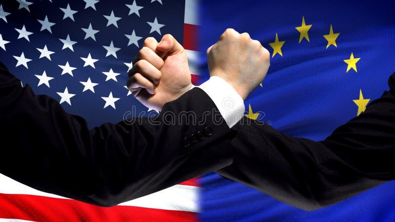 US gegen EU-Konfrontation, Landwiderspruch, Fäuste auf Flaggenhintergrund stockfoto