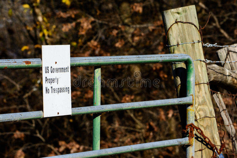US Government Property sign on locked gate with thick woods in b. Ackground. Regulation, litigation, obstruction, barriers, imminent domain stock photo