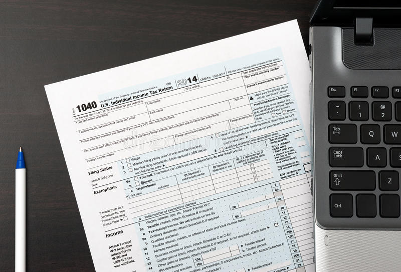 US Individual Tax Return Form 1040 on a table with laptop and pen. US Individual Tax Return Form 1040 on a table next to laptop computer and pen royalty free stock photos