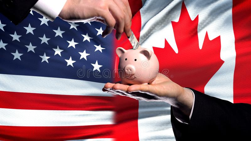 US investment in Canada, hand putting money in piggybank on flag background stock photo