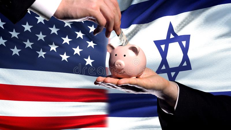 US investment in Israel, hand putting money in piggybank on flag background. Stock photo royalty free stock photo