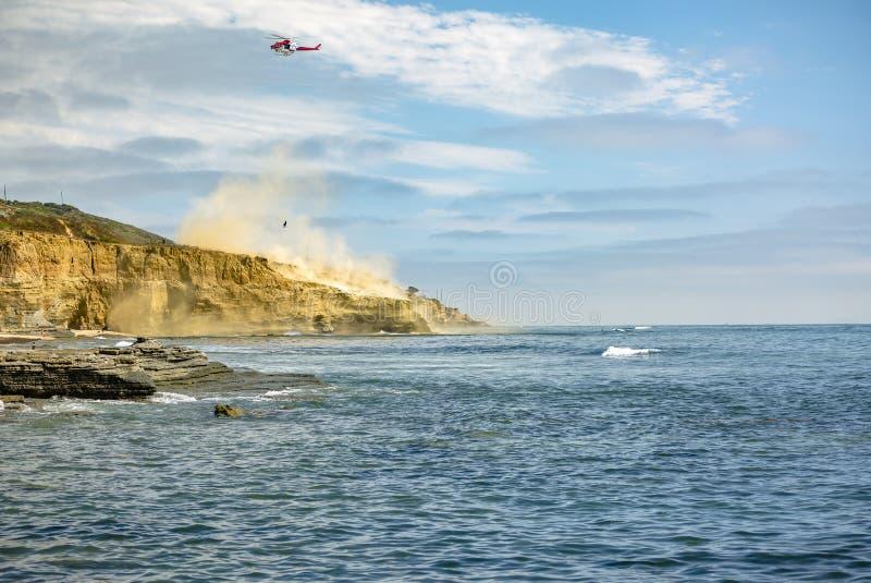 US-Küstenwachenhubschrauber im Flug, Point Loma-Strand mit Staub lizenzfreie stockfotos