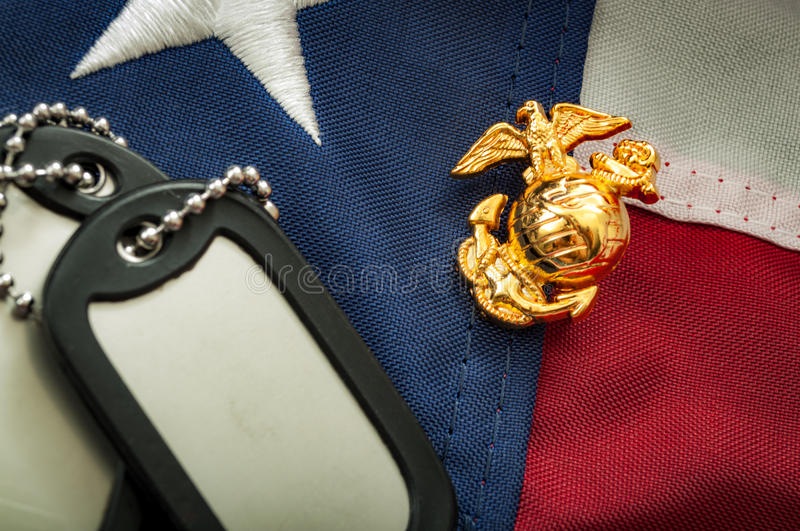 US Marine corps emblem, military dog tags and the American flag. Macro image of the US Marine Corps emblem on the American flag next to military dog tags royalty free stock photography