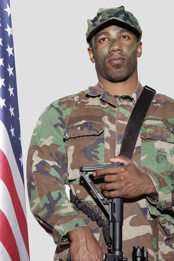US Marine Corps soldier with M4 assault rifle standing by American flag over gray background stock photo