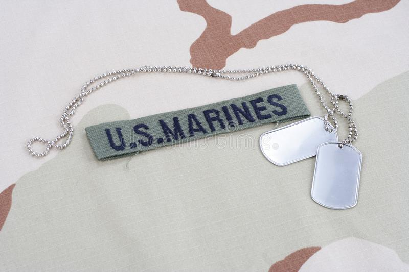 US MARINES branch tape with dog tags on desert camouflage uniform. Background stock image