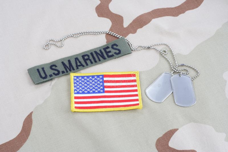 US MARINES branch tape with dog tags and flag patch on desert camouflage uniform. Background royalty free stock photography