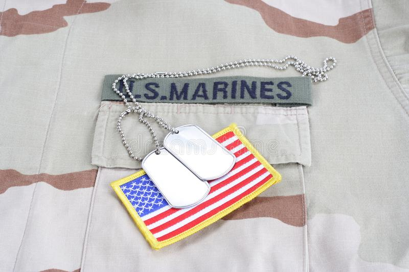 US MARINES branch tape with dog tags and flag patch on desert camouflage uniform. Background stock photography