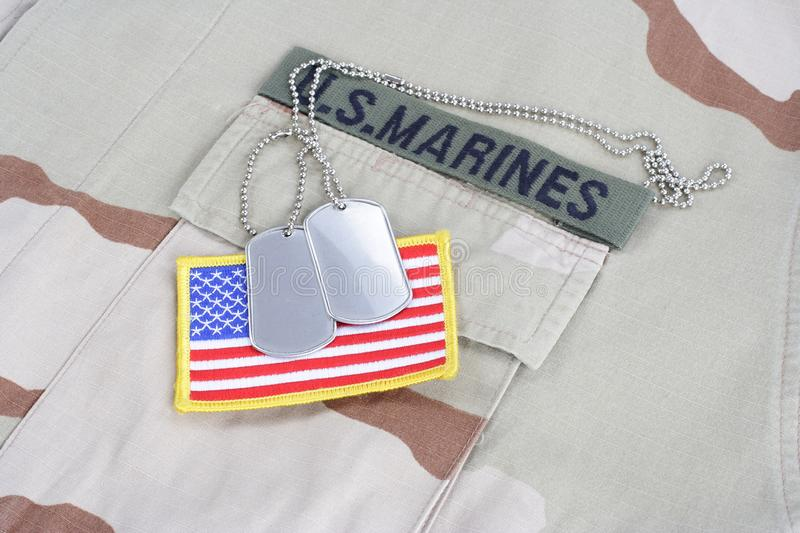 US MARINES branch tape with dog tags and flag patch on desert camouflage uniform. Background royalty free stock image