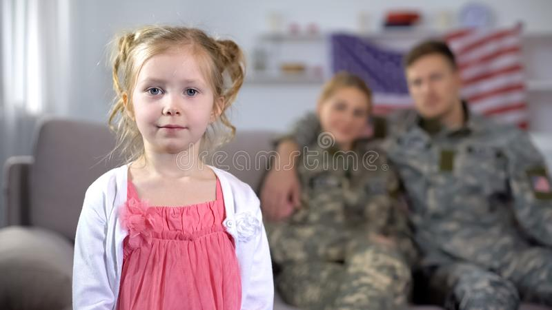 US military couple admiring little cute daughter looking at camera, family. Stock photo royalty free stock image