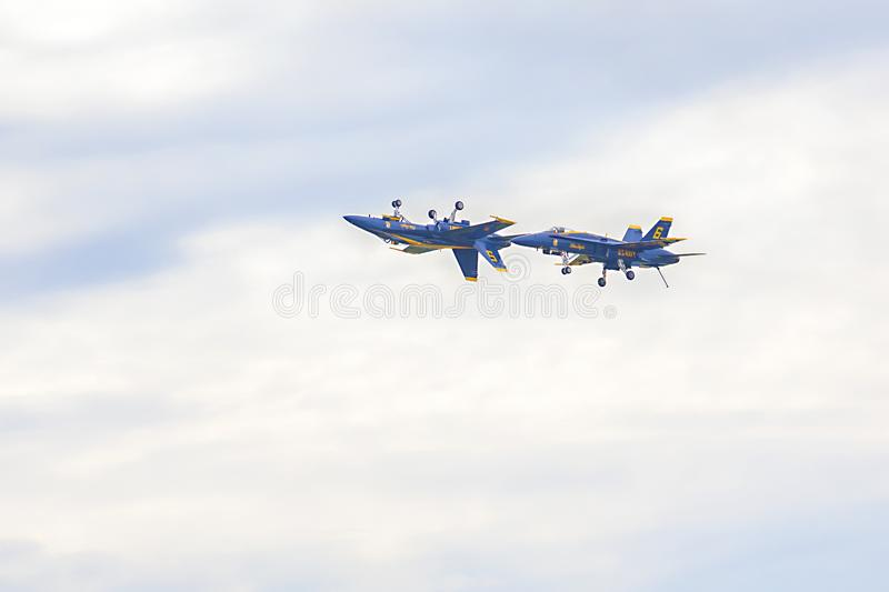 US Navy Blue Angels Hornet Fighter Jets Flying At Close Proximity With One Being Inverted. During an air show at McDill Air Force Base in Tampa, Florida stock photos