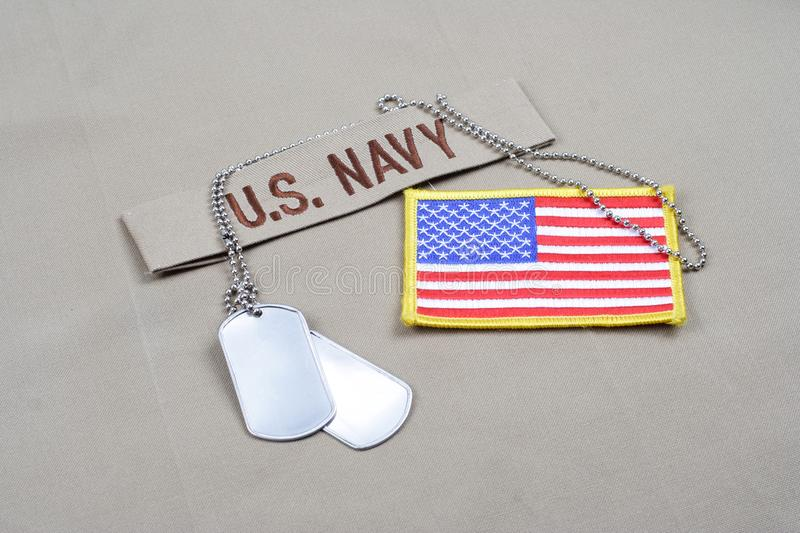 US NAVY branch tape with dog tags and US flag patch on desert camouflage uniform. Background stock photography