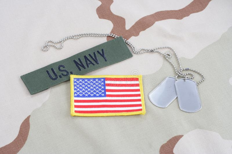 US NAVY branch tape with dog tags and flag patch on desert camouflage uniform. Background stock photo