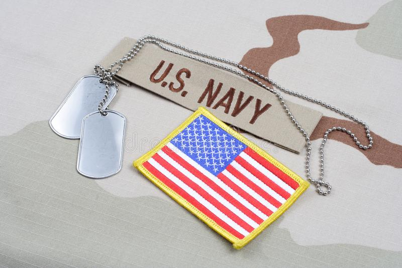 US NAVY branch tape with dog tags and US flag patch on desert camouflage uniform. Background stock photos