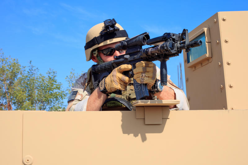 US Navy EOD aims rifle from a military humvee stock photo