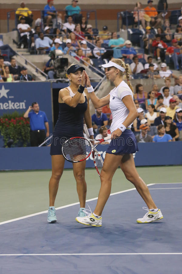 US Open 2014 women doubles champions Ekaterina Makarova and Elena Vesnina during final match. NEW YORK - SEPTEMBER 6, 2014: US Open 2014 women doubles champions stock image