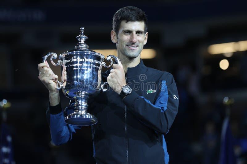US Openmästare 2018 Novak Djokovic av Serbien som poserar med US Opentrofén under trofépresentation efter hans finalmatchseger arkivbild