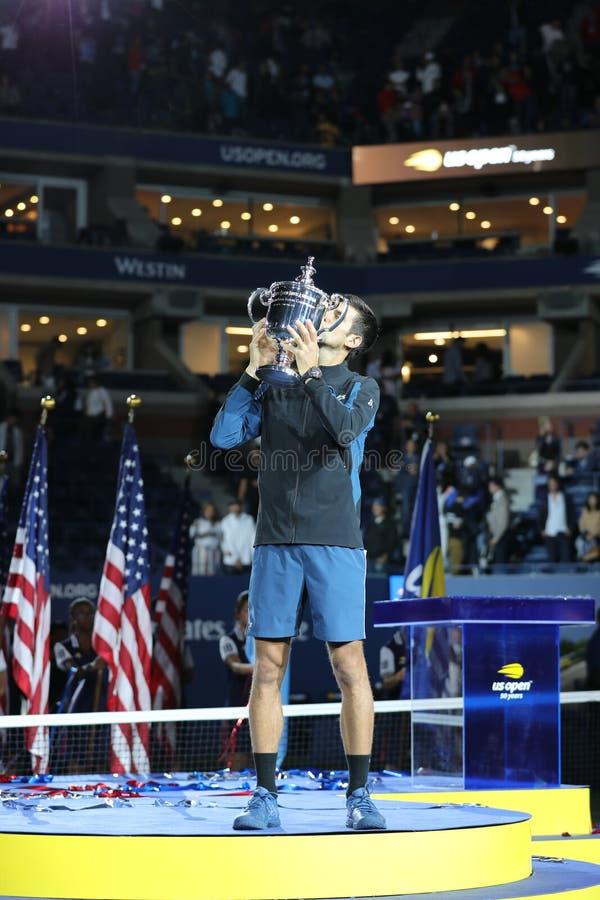 US Openmästare 2018 Novak Djokovic av Serbien som poserar med US Opentrofén under trofépresentation efter hans finalmatchseger royaltyfri bild