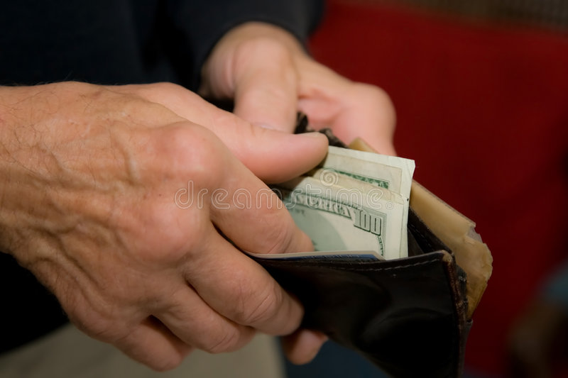 US paper money in wallet. Man getting US paper money from worn wallet or billfold royalty free stock image
