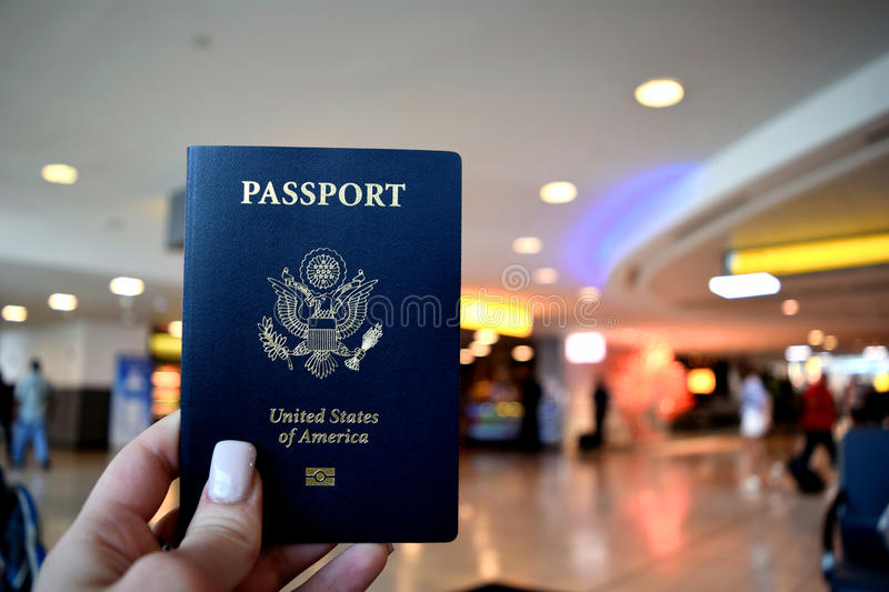 US Passport. A US passport with an airport lobby in the background stock image