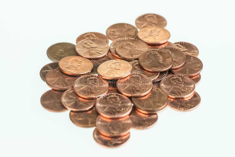 US pennies piled up. US one cents piled up over white background royalty free stock photo