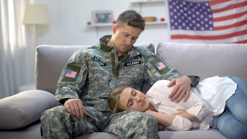 US soldier stroking head of sleeping on his knees girlfriend, care and love. Stock photo royalty free stock photo